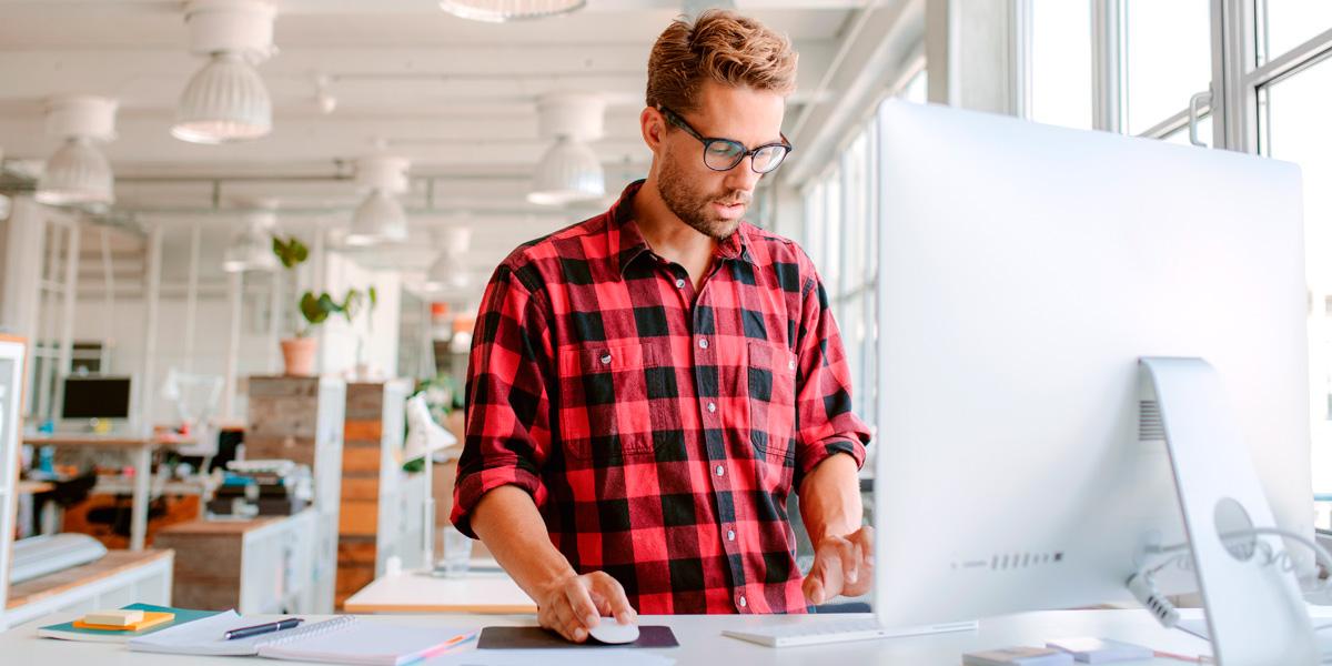 Chico joven utilizando pc en oficina para diseño web WordPress
